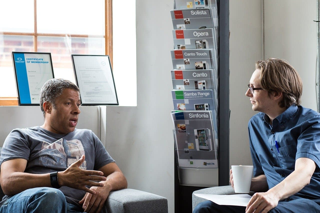 two men having a conversation in an office