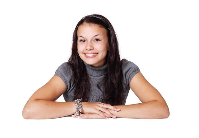 girl sitting at table and smiling as if trying to look innocent