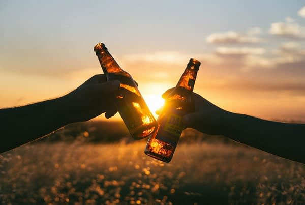 two people clinking beer bottles together at sunset, related to beer marketing
