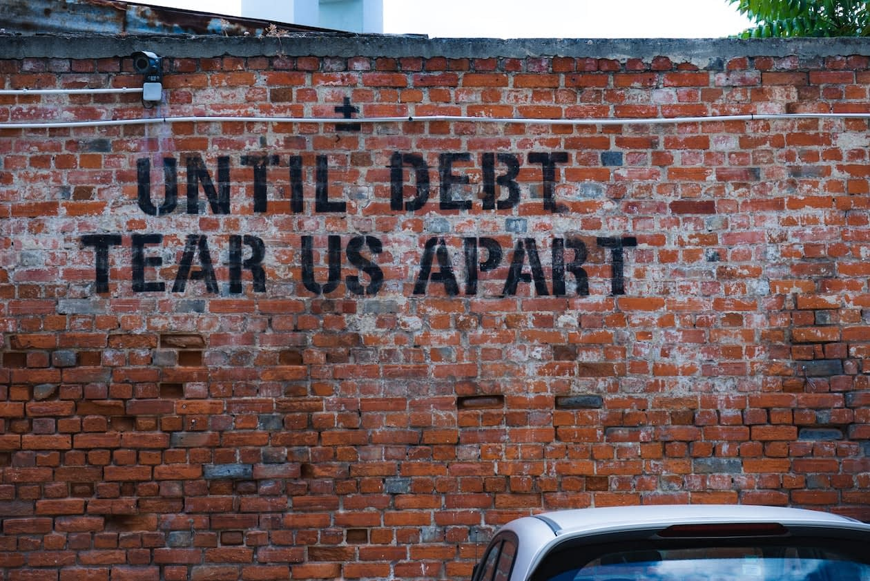 writing spray painted on a brick wall that says until debt tear us apart