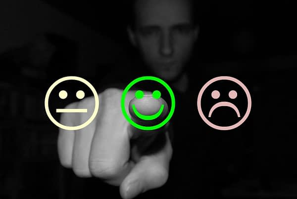 man selecting happy face from 3 smily faces (happy, sad and neutral)