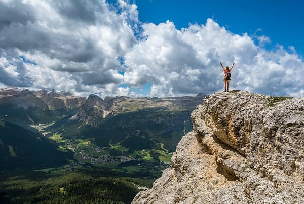 person standing on the top of a mountain with their arms up to the sky symbolizing success