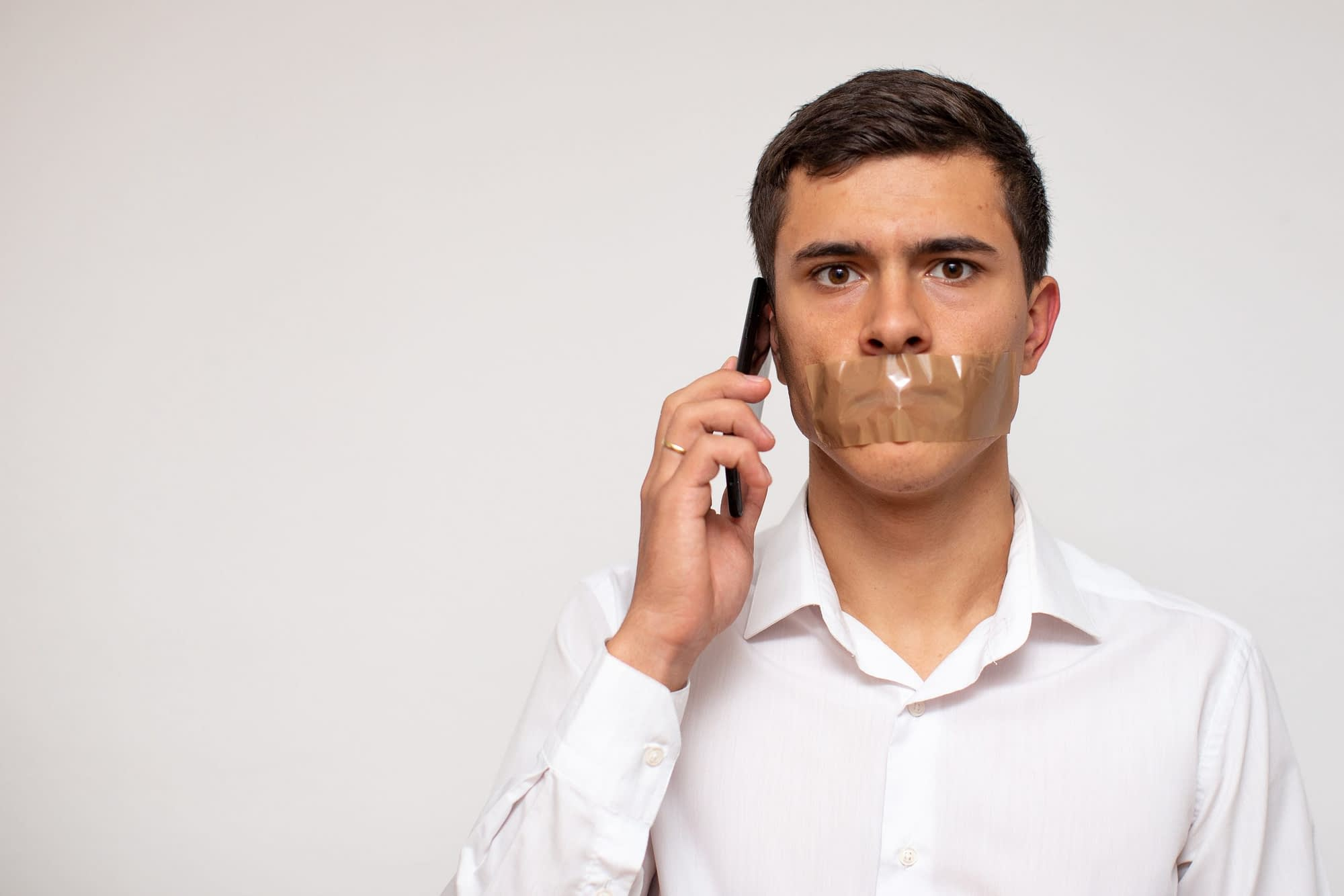 a guy on the phone with tape covering his mouth so he can't speak