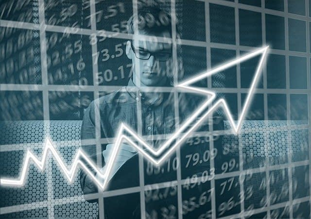 man standing behind a chart with statistics with an arrow going up indicating success