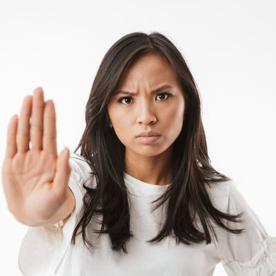 "woman putting up her hand as if to say ""no"""