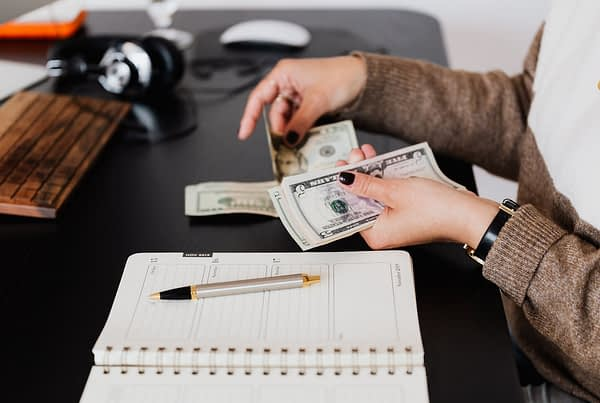 person counting money at a desk